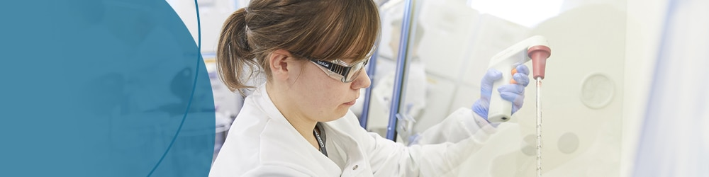 Scientist working in cell culture hood